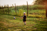 Picture of a small boy playing in a yard with his rabbit. Pets are best friends. - 222990984
