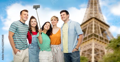 travel, tourism and technology concept - group of happy smiling friends taking selfie by smartphone over eiffel tower background