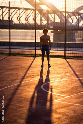Mięśni Yong pasuje półnagi mężczyzna stojący na zewnątrz i przygotowuje swój umysł do ciężkiego treningu.