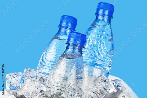 Three Bottles of Water in Ice Bucket on the Blue Background - 222995740