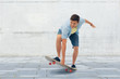 sport, leisure and skateboarding concept - smiling young man riding skateboard over urban street background