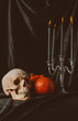 skull, pumpkins and candelabrum with candles on black cloth