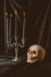 creepy skull and candelabrum with black candles on dark cloth for halloween