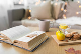 hygge and cozy home concept - book, autumn leaves, cup of tea with lemon, almond nuts and oatmeal cookies on table - 222997166