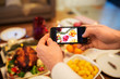 technology, eating and holidays concept - close up of male hands photographing food by smartphone at christmas dinner