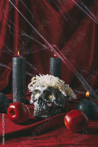 srebrna czaszka z kwiatami, świecami i jabłkami na czerwonym obrusie z pajęczyną