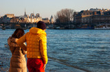Unrecognizable couple (back view) admiring high water in Seine river at golden sunset. Winter flood in Paris, France.