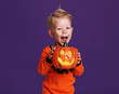 happy Halloween! cheerful child boy in costume with pumpkins on violet purple background