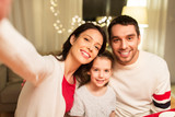 family, christmas and holidays concept - happy mother, father and little daughter taking selfie at home - 222999338
