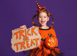 happy Halloween! cheerful child girl in costume with pumpkins on violet purple background