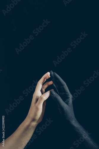 cropped view of woman touching with black demon hand isolated on black - 222999913