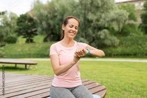 Sticker sport and technology concept - smiling woman with fitness tracker in park