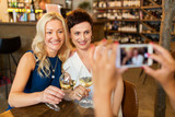people, technology and lifestyle concept - woman photographing friends drinking wine by smartphone at bar or restaurant - 223002788