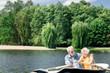 Enjoying boating. Peaceful beautiful senior couple smiling and enjoying boating while hugging in the boat