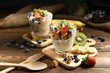 Yogurt with granola and fruits in glass on wooden table