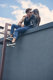 bottom view of stylish sexy multiethnic couple going to kiss while sitting on roof