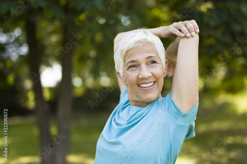 Foto Murales Senior woman doing exercise for stretching hand in the park