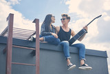 happy multicultural couple sitting on roof with acoustic guitar