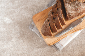 Fresh sliced loaf of rye bread on the wooden cutting board background