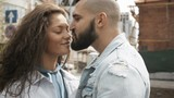Beautiful young woman and bearded man kissing with love standing on street - 223013339