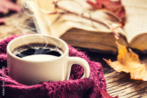 Cup of coffee old  book glasses and autumn leaves.