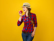 smiling young woman grower on yellow background eating an apple