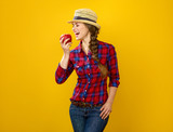 smiling young woman grower on yellow background eating an apple - 223018503