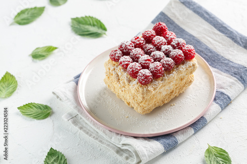Napoleon cake with raspberries on a white table - 223024584