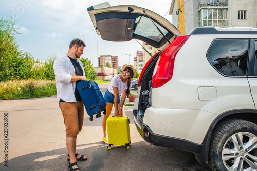Wall mural car travel concept. opened trunk with luggage inside woman with
