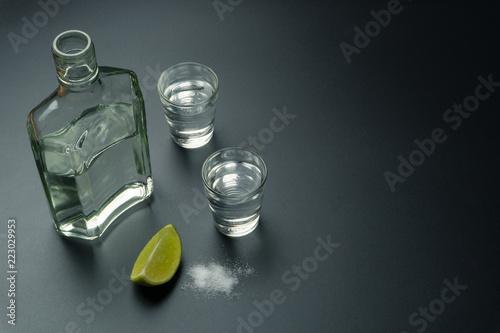 butelka srebrnej tequili z dwoma kieliszkami do tequili, plasterkiem limonki i solą na stole