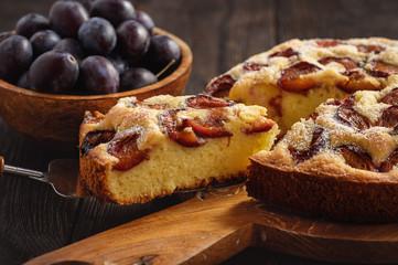 Homemade plum cake on dark wooden background.