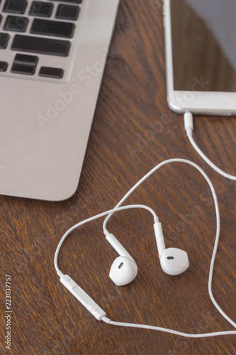 Business concept: Phone with headphones on the table. Close-up - 223037757