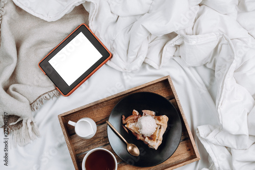 Cozy flatlay of bed with wooden tray with vegan apple pie, ice cream, black tea and tablet or ebook with white copyspace screen on white sheets and blankets - 223045787