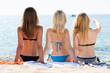 Girls wearing swimwear sitting back-first