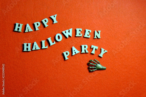 Inscription HAPPY HALLOWEEN PARTY made of wooden letters on an orange background. The claw of the monster lies next to the words in the form of waves. Copy space. - 223048562