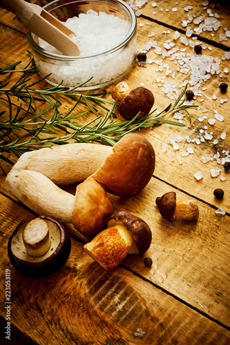 delicious fresh various mushrooms on an old wooden table with salt and rosemary - 223053119