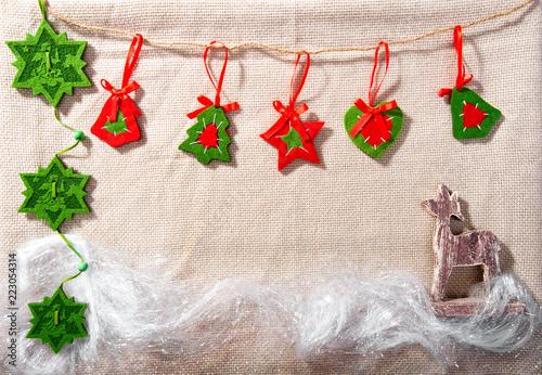 ręcznie robiona kartka świąteczna z filcowanymi gwiazdkami, płatki śniegu i dekorowanie choinki, renifer, błyszcząca błyskotka na beżowym tle tkaniny wełnianej