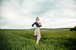 Young girl in a green field. Stylish girl. Green grass and blue sky. Emotional woman. plener. Travel. trip.