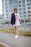 Beautiful woman with nude legs walking around city street wearing long white shirt