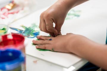 Closeup of toddler making palm print on paper
