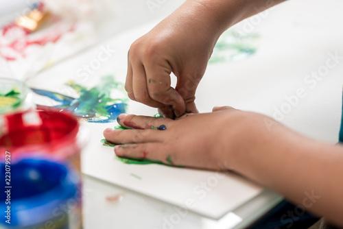 Fototapeta Closeup of toddler making palm print on paper