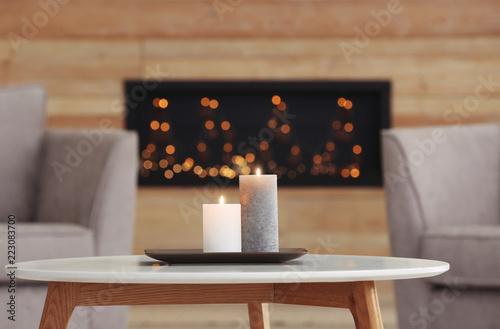 Leinwandbild Motiv Plate with burning candles on table in living room