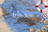 Maritime Dekoration auf blauem Holzuntergrund mit Umriß der Insel Usedom und Beschriftung