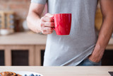 traditional morning hot beverage. quick and easy breakfast. man holding tea or instant coffee drink in a red mug standing in the kitchen. - 223107724