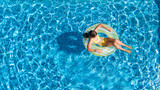 Aerial drone view of little girl in swimming pool from above, kid swims on inflatable ring donut , child has fun in blue water on family vacation resort