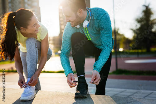Young fitness couple running in urban area - 223123950