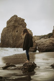 Woman standing alone on the beach - 223138185