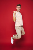 Full length photo of successful man in striped t-shirt screaming and clenching fists, isolated over red background - 223143365