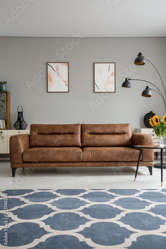 Blue Patterned Carpet And Leather Sofa In Grey Living Room Interior With  Posters And Lamp.