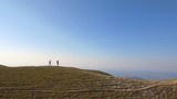 Two men hiking on the ridge at the top of mountain - 223146741